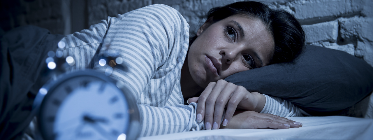 Image of woman looking sleepless with clock at the front