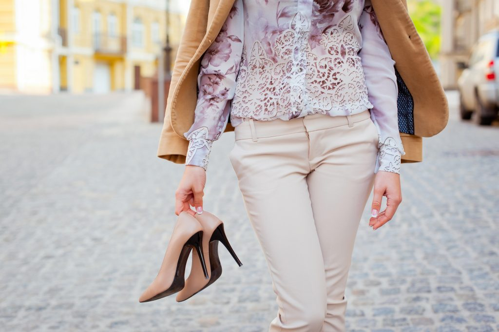 woman carrying nude colored shoes